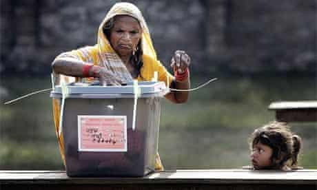 A Nepalese woman casts her vote as a girl looks on at a polling station in Janakpur, 385km (240 miles) east of Kathmandu