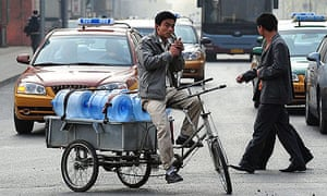 A water deliveryman has a smoke while stuck in traffic in Beijing.