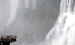 Tourists stand at the edge of an observation deck over the Iguazu river to watch the Devil's Throat cascade