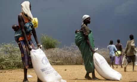 Two Ugandan women drag sacs with food relief