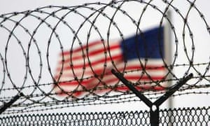 A US flag waves within the razor wire-lined compound of Camp Delta prison at Guantánamo Bay in 2006