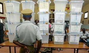 A police officer stands in front of stacked ballot boxes in Zimbabwe