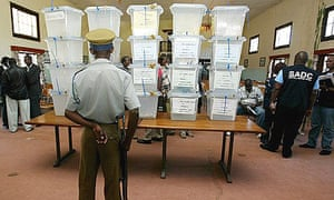 A police officer looks on as ballot boxes are pilled up on a table at the Domboshava training centre, Zimbabwe.