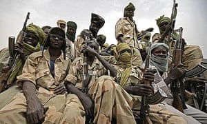 Fighters from the Justice and Equality Movement (JEM) riding in the back of an armoured vehicle in Darfur.