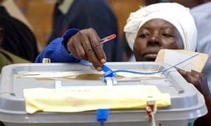 A polling agent inspects a ballot box during the Zimbabwe recount
