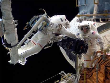 Space shuttle astronauts repair the Hubble Space Telescope