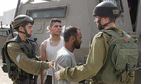 Israeli soldiers take in people for questioning after two guards were shot dead by Palestinian militants in an industrial zone near Nitzanei Oz, in the West Bank.