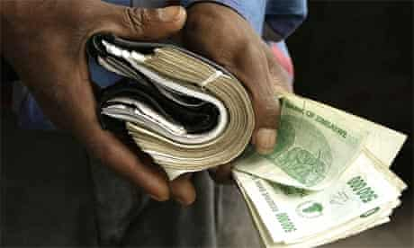A Zimbabwean man shows his overloaded wallet in Harare, Zimbabwe