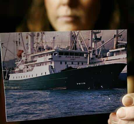 The daughter of one of the crew members of Playa de Bakio, a Spanish vessel hijacked by Somali pirates, holds a photograph of the boat