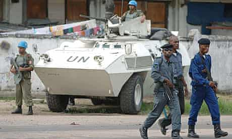 Congolese police walk past a United Nations patrol in Kinshasa.