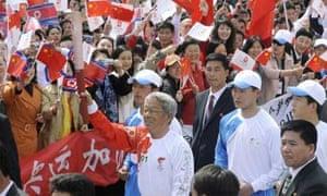 Former North Korean national soccer team player Pak Doo-ik carries the flame through Pyongyang