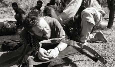 John D McHugh grimices in pain as a medic examines and dresses his gunshot wound at Kamu outpost in Nuristan, Afghanistan, May 14 2007