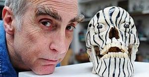 Artist Stephen Gregory in his studio with one of his jewel-encrusted skulls
