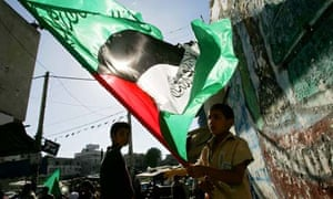 Children hold Palestinian flags in front of the mosque in Beit Lahia, Gaza