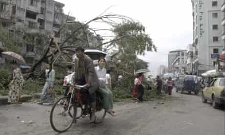 Rangoon, Burma: A bicycle taxi driver carries a passenger through a damaged area of the city