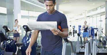 A man walking on treadmill reading the paper