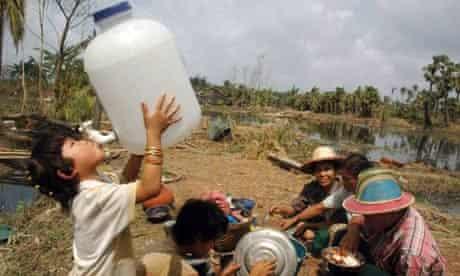A girl drinks water in Konegyangone township, Burma