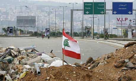 A flag flutters on a mound of earth blocking the main road leading to Rafiq Hariri International airport in Beirut