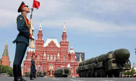 An honour guard stands to attention as missile carriers rumble through Red Square, Moscow, in a return of the Victory Day parade