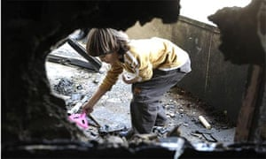 A young boy plays in a house damaged by shells during clashes between pro-government supporters and Hizbullah gunmen