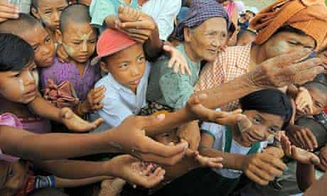 Cyclone survivors reach out for food aid in Rangoon. The UN said it was delivering only a fraction of the emergency rations needed