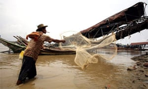A man throws a net into water beside a wharf damaged by cylone Nargis in Burma