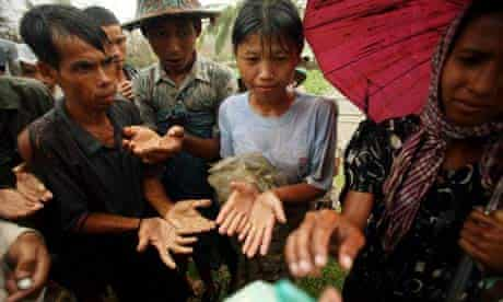 Burmese people beg for food in the rain as aid begins to arrive following cyclone Nargis