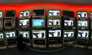 A wall of TV screens in a Currys store in London