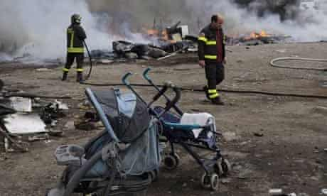 Firefighters inspect the remains of a Gypsy camp set alight in Naples