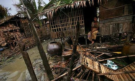 A woman sits outside her ruined home on the outskirts of Rangoon, Burma