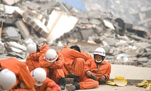 Rescue workers take a break in the devastated town of Beichuan