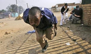People run from police firing rubber bullets in the Reiger Park informal settlement outside Johannesburg, South Africa