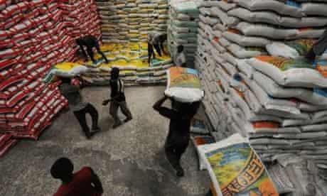Workers handle sacks of imported rice in Abidjan, Ivory Coast