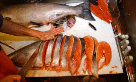 A salmon is cut into steaks at the Pike Place fish market in Seattle. Photograph: Elaine Thompson/AP