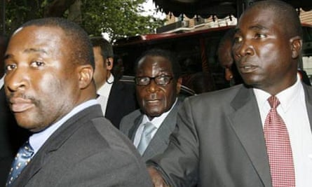 Bodyguards escort Robert Mugabe into his hotel for the UN world food summit  in Rome