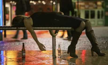 A young woman lies on a bench surrounded by alcohol bottles after a night binge drinking