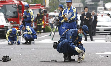 Police officers search for clues in Tokyo's Akihabara shopping and amusement district after at least five people were killed by a man who went on a knife rampage