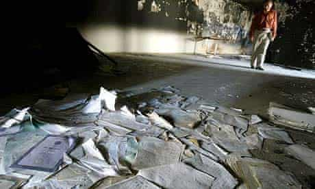 A man stands near a pile of papers in the ruins of the national library in Bagdhad, Iraq, which was burned and looted in 2003