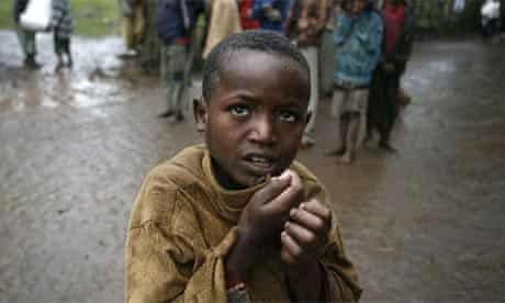 A boy shivers in the rain as villagers carry sacks of maize received from the Red Cross in the Volayta region of southern Ethiopia