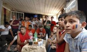 Roma gypsies near Milan watch the Italy-Romania game