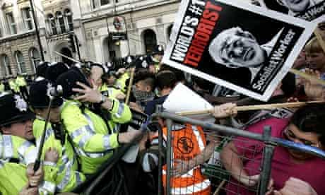 British police officers, left, clash with anti-war protesters gathered at Parliament Square in London during George Bush's visit