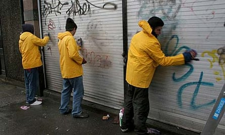 Offenders doing community service, removing graffiti
