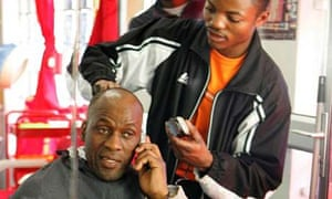 A Cape Town resident is seen chatting on his mobile phone, reflected in the mirror at a barber's shop