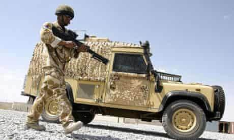 """British soldiers practise """"actions on contact with the enemy"""" drill using their Snatch Land Rover vehicles at a base in Lashkar Gah, Helmand province"""