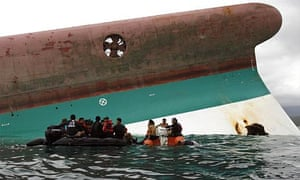 Divers on a rubber boat wait beside the capsized ferry MV Princess of Stars, off Sibuyan island