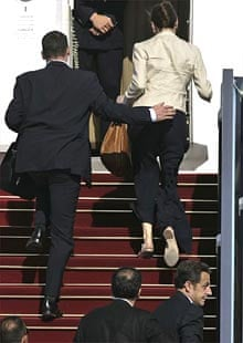 The French president, Nicolas Sarkozy (bottom right), and his wife, Carla Bruni-Sarkozy (top right), are rushed onto an airplane by security during a departure ceremony at Ben Gurion airport in Tel Aviv