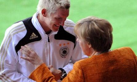 German Chancellor Angela Merkel jokes with footballer Bastian Schweinsteiger at Euro2008