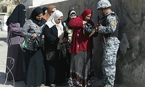 An Iraqi police officer stops residents at a checkpoint outside a school in Mahmudiya, 20 miles south of Baghdad.