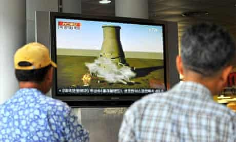 South Koreans at a railway station in Seoul watch a video showing a simulation of the planned blow-up of a cooling nuclear tower at North Korea's Yongbyon nuclear complex