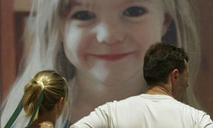 Parents of missing child Madeleine McCann, Kate and Gerry McCann look at a giant billboard of her daughter on the beach near the Portuguese resort of Lagos